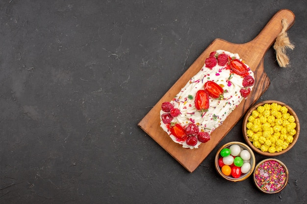 Vue de dessus d'un délicieux gâteau aux fruits avec des bonbons sur fond noir