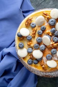 Vue de dessus délicieux gâteau aux noix, myrtilles et biscuits surface sombre