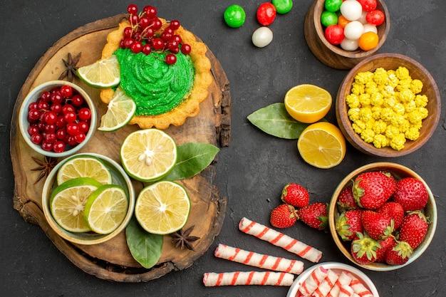Vue de dessus délicieux gâteau avec des bonbons et des fruits sur fond sombre biscuit biscuit sucré