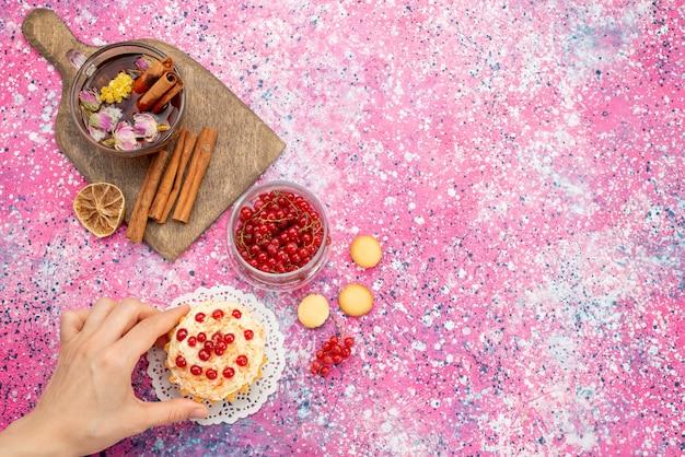 Vue de dessus délicieux gâteau à la crème avec des canneberges rouges fraîches avec de la cannelle et du thé sur le bureau violet sucre sucré
