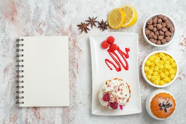 Vue de dessus délicieux gâteau crémeux au citron et bonbons sur fond blanc biscuit crème gâteau thé bonbons