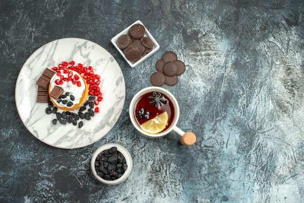 Vue de dessus délicieux gâteau crémeux avec des biscuits au chocolat et une tasse de thé sur le fond clair-foncé