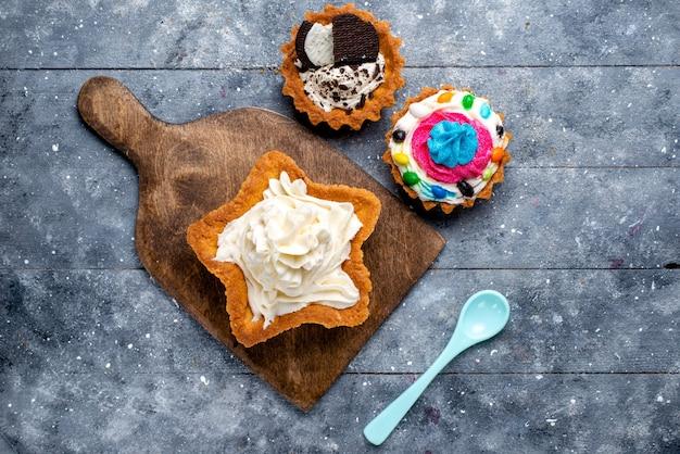 Vue de dessus délicieux gâteau crémeux en forme d'étoile avec des gâteaux aux biscuits et cuillère bleue sur le fond clair gâteau biscuit crème thé sucré