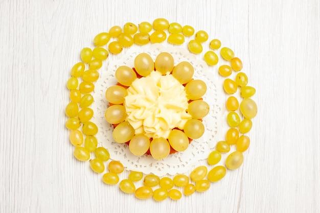 Vue de dessus délicieux gâteau crémeux avec des raisins verts frais sur un bureau blanc gâteau à la crème de fruits biscuit biscuit