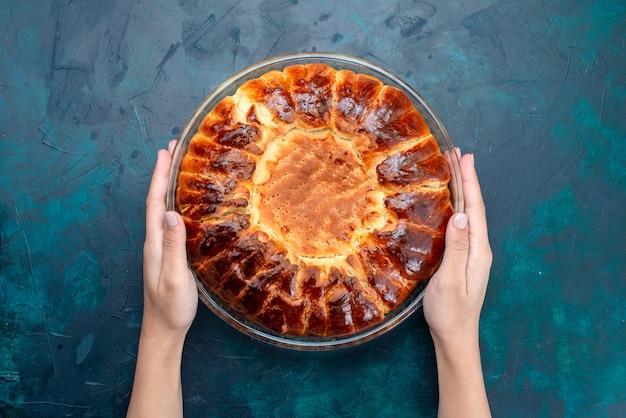 Vue de dessus délicieux gâteau cuit rond formé doux à l'intérieur de la casserole en verre sur le fond bleu clair.