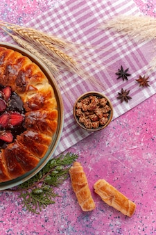 Vue de dessus délicieux gâteau fruité tarte aux fraises avec des bagels sur rose