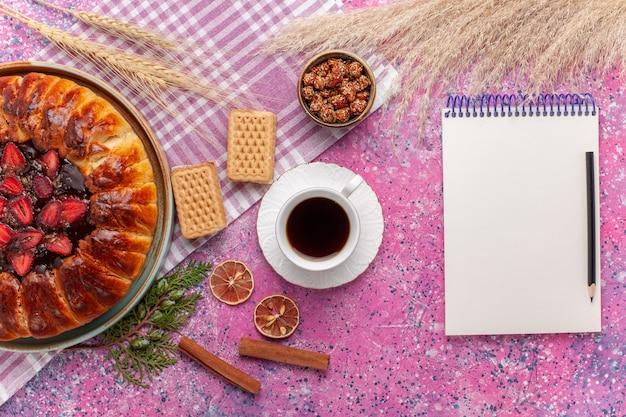 Vue de dessus délicieux gâteau fruité tarte aux fraises avec tasse de thé sur le rose