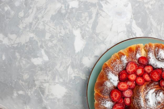Vue de dessus délicieux gâteau en poudre de sucre tarte aux fraises sur fond blanc