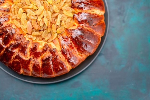 Vue de dessus délicieux gâteau rond formé sucré avec des raisins secs sur le bureau bleu clair.