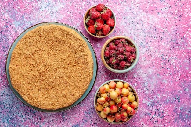 Vue de dessus délicieux gâteau rond à l'intérieur de la plaque avec des fruits sur le bureau rose vif gâteau tarte biscuit sucré cuire au four