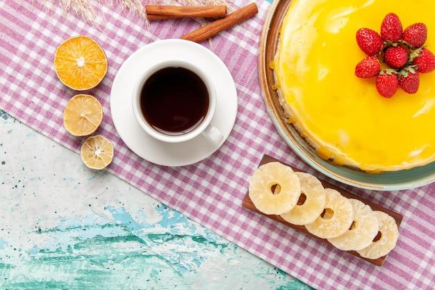 Vue de dessus délicieux gâteau avec sirop jaune tasse de thé et fraises fraîches sur la surface bleu clair biscuit gâteau biscuits tarte sucrée thé au sucre