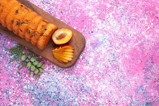 Vue de dessus délicieux gâteau sucré et délicieux avec des prunes sur le bureau rose.