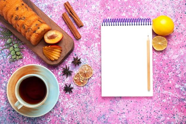 Vue de dessus délicieux gâteau sucré et délicieux avec une tasse de thé et de cannelle sur le bureau rose.