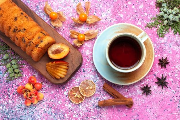 Vue de dessus délicieux gâteau sucré et délicieux avec une tasse de thé et de cannelle sur le fond rose.