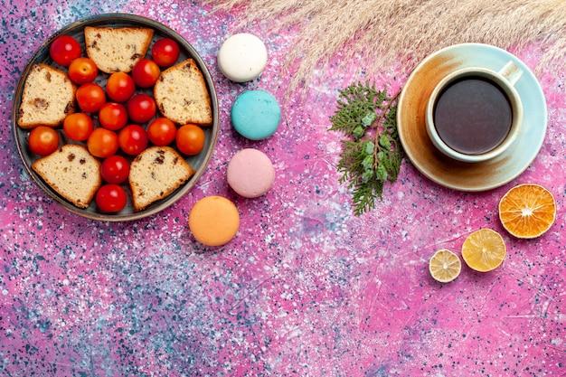 Vue de dessus délicieux gâteau tranché avec macarons de prunes fraîches aigres et tasse de thé sur le bureau rose