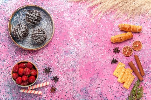 Vue de dessus de délicieux gâteaux au chocolat avec des bagels sur rose