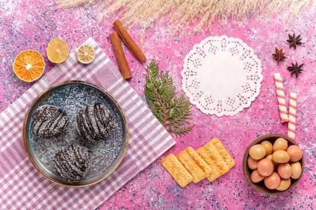Vue de dessus de délicieux gâteaux au chocolat avec des bonbons et des chips sur un rose