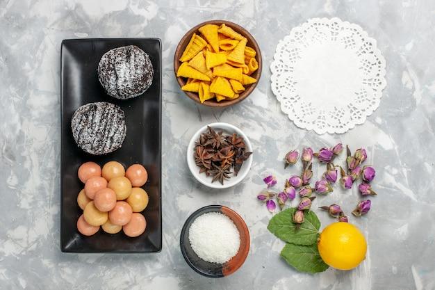 Vue de dessus de délicieux gâteaux au chocolat avec des craquelins sur un biscuit de surface blanc clair cuire un gâteau au sucre sucré
