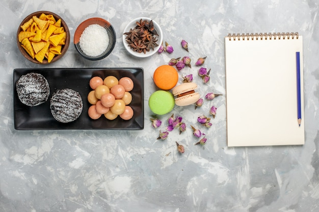 Vue de dessus de délicieux gâteaux au chocolat avec des craquelins et des macarons sur un biscuit de bureau blanc clair cuire un gâteau au sucre sucré