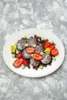 Vue de dessus de délicieux gâteaux au chocolat avec des fraises fraîches sur la surface blanche biscuit gâteau au sucre biscuit au thé sucré
