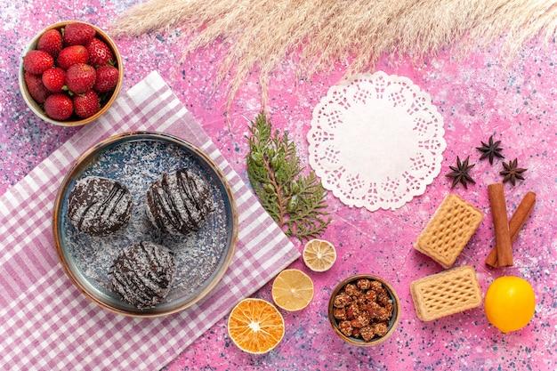 Vue de dessus de délicieux gâteaux au chocolat avec des fraises rouges fraîches sur rose