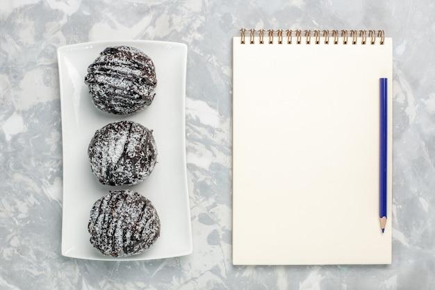 Vue de dessus de délicieux gâteaux au chocolat avec glaçage blanc sur la surface blanc-clair gâteau biscuit cuire au chocolat thé au sucre sucré