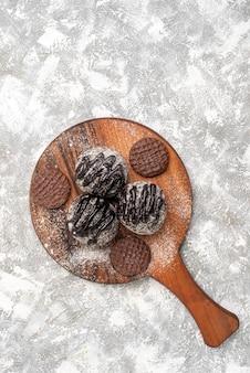 Vue de dessus de délicieux gâteaux aux boules de chocolat avec des biscuits sur une surface blanche