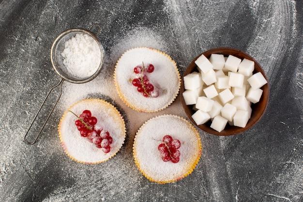 Vue de dessus de délicieux gâteaux aux canneberges cuits au four et délicieux avec des morceaux de sucre de canneberges rouges sur le dessus de gâteau de bureau gris biscuit sucre sucré