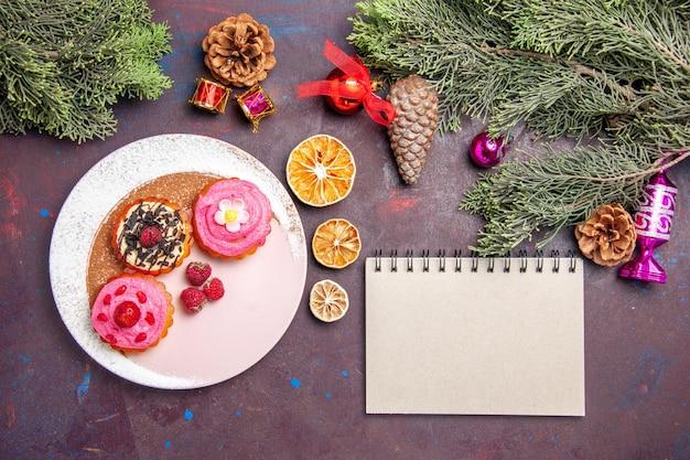Vue de dessus de délicieux gâteaux aux fruits et à la crème sur fond noir