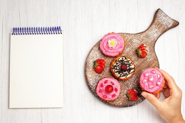 Vue de dessus de délicieux gâteaux aux fruits desserts crémeux avec des fruits sur fond blanc thé à la crème gâteau au dessert sucré cookie