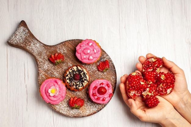 Vue de dessus de délicieux gâteaux aux fruits desserts crémeux avec des grenades sur fond blanc thé à la crème gâteau au dessert sucré cookie