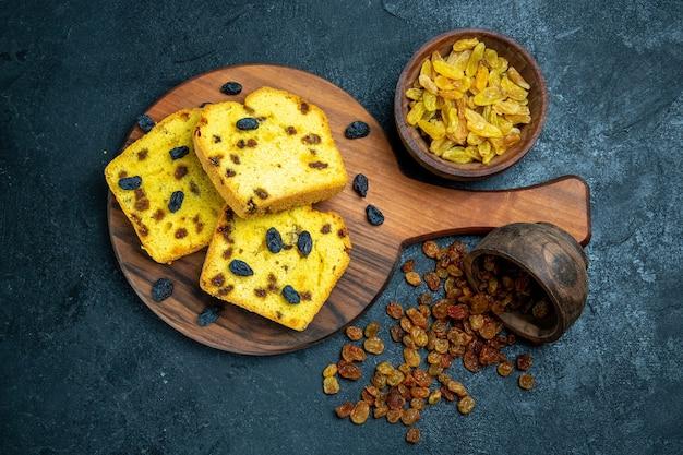 Vue de dessus de délicieux gâteaux aux raisins secs tranchés avec des raisins secs frais sur un espace bleu foncé