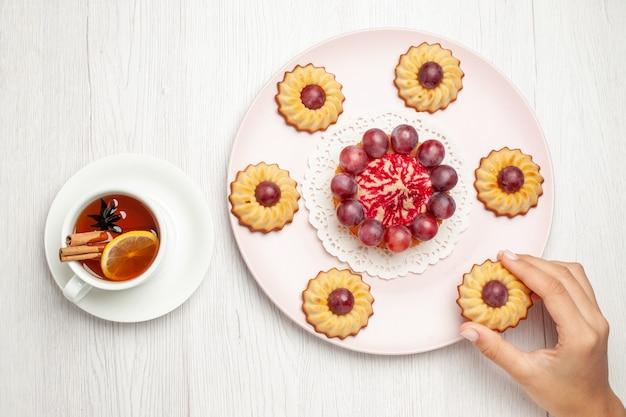 Vue de dessus de délicieux gâteaux aux raisins avec une tasse de thé sur la table blanche biscuit tarte biscuit biscuit