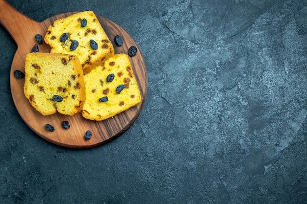 Vue de dessus de délicieux gâteaux aux raisins en tranches sur un espace bleu foncé