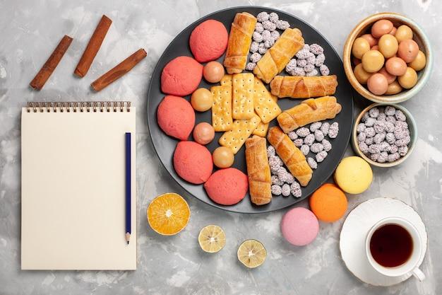 Vue de dessus de délicieux gâteaux avec des bagels, des bonbons, des biscuits et du thé sur le gâteau de bureau blanc clair biscuit biscuit tarte au sucre