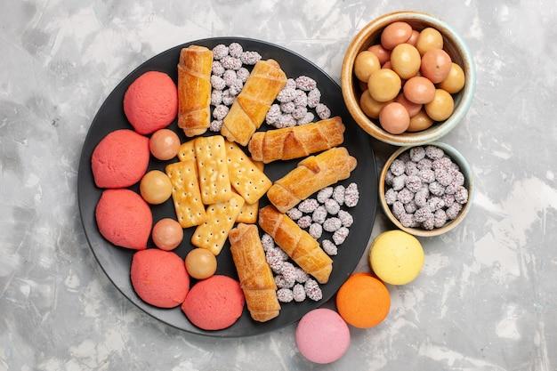 Vue de dessus de délicieux gâteaux avec des bagels bonbons craquelins sur un gâteau de bureau blanc clair biscuit biscuit tarte au sucre douce