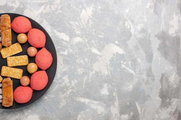 Vue de dessus de délicieux gâteaux avec des bagels et des bonbons sur une surface blanche grise