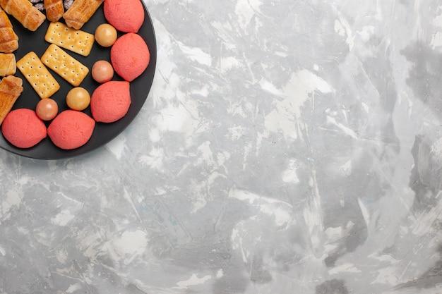 Vue de dessus de délicieux gâteaux avec des bagels et des bonbons sur une surface blanche