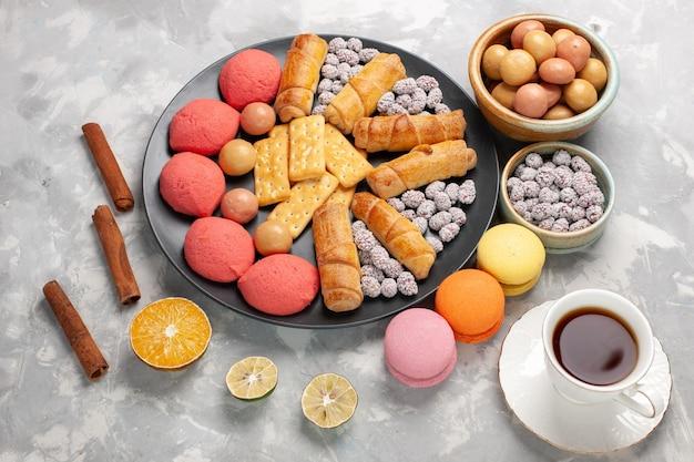 Vue de dessus de délicieux gâteaux avec des bagels de thé, des bonbons craquelins sur le gâteau de bureau blanc clair biscuit biscuit tarte au sucre sucré