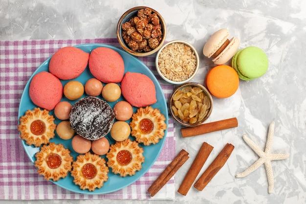 Vue de dessus de délicieux gâteaux avec biscuits raisins secs et macarons sur surface blanche