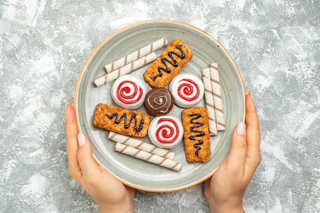 Vue de dessus de délicieux gâteaux et biscuits sucrés sur un espace blanc