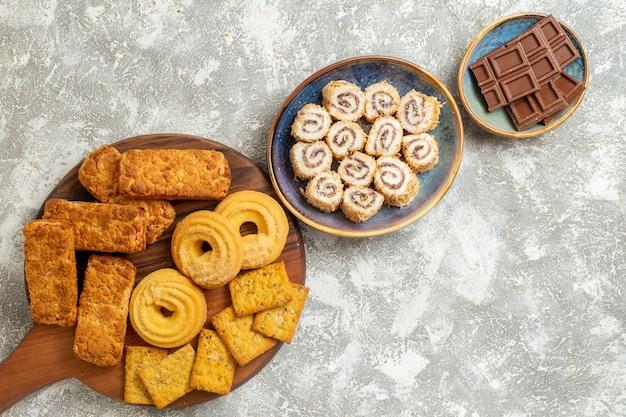 Vue de dessus de délicieux gâteaux avec des bonbons et des biscuits sur fond blanc