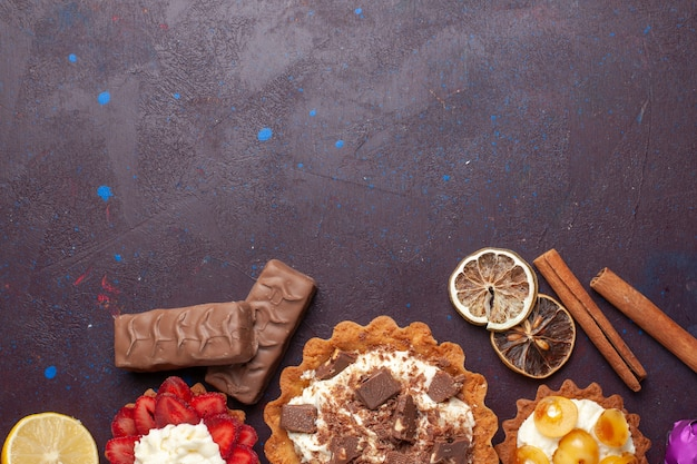 Vue de dessus de délicieux gâteaux avec de la cannelle et des bonbons sur la surface sombre