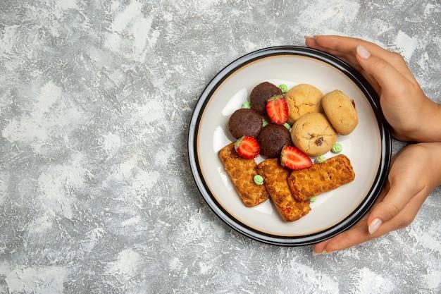 Vue de dessus de délicieux gâteaux avec des cookies et des fraises sur fond blanc biscuit gâteau au sucre tarte sucrée biscuit au thé