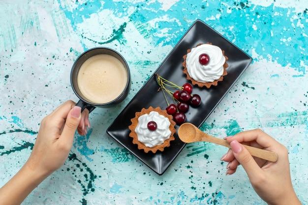 Vue de dessus de délicieux gâteaux à la crème et aux fruits sur la surface de la lumière bleue gâteau crème douce cuire le thé aux fruits