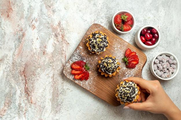 Vue de dessus de délicieux gâteaux crémeux avec des fraises tranchées sur une surface blanche biscuit de thé d'anniversaire crème de gâteau sucré