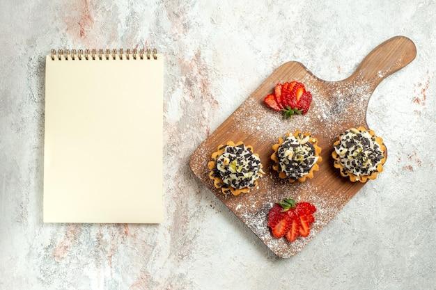 Vue de dessus de délicieux gâteaux crémeux avec des fraises tranchées sur une surface blanche gâteau au thé à la crème biscuit anniversaire sucré