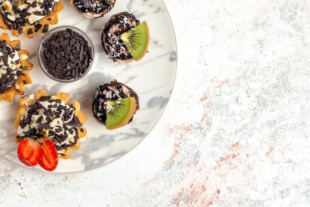 Vue de dessus de délicieux gâteaux crémeux petits desserts pour le thé avec des pépites de chocolat sur une surface blanche gâteau aux fruits crème biscuit tarte thé