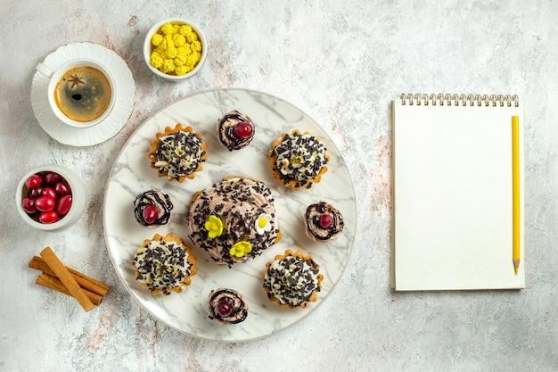 Vue de dessus de délicieux gâteaux crémeux avec une tasse de café sur une surface blanche gâteau au thé biscuit crème d'anniversaire douce