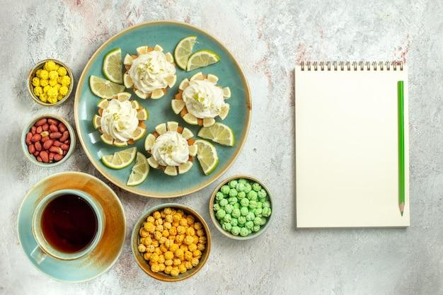 Vue de dessus de délicieux gâteaux crémeux avec des tranches de citron et des bonbons sur une surface blanche gâteau biscuit biscuit thé crème douce